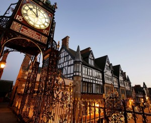 City of Chester, England. Night photograph of the Eastgate Clock above Eastgate Street on Chester's city walls, with of Eastgate Street in the background.